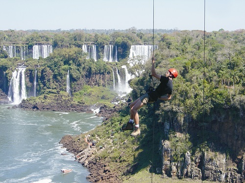 Man dangling from a rope in mid-air with rainforest waterfalls behind