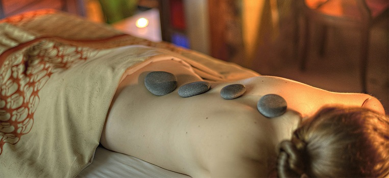 Woman lying prone with round stones on her back