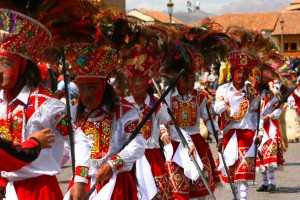 Five colourful figures with traditional ornate headpieces and masks, red and white clothing