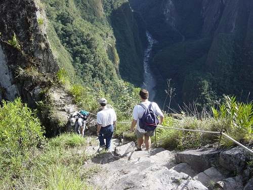 People walking down extremely steep steps in a mountain ravine