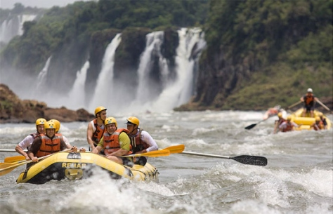Two kayaks in white water with waterfall behind