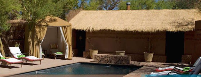 Small pool area surrounded by sunbeds, terracotta-coloured walls and a thatched lodge at the end.