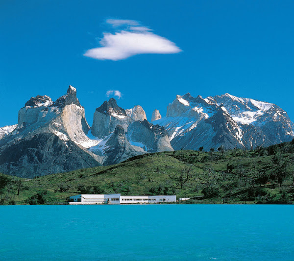 Looking across a rich turquoise lake, against the backdrop of high mountains, a hotel sits at the foothills on the shore.