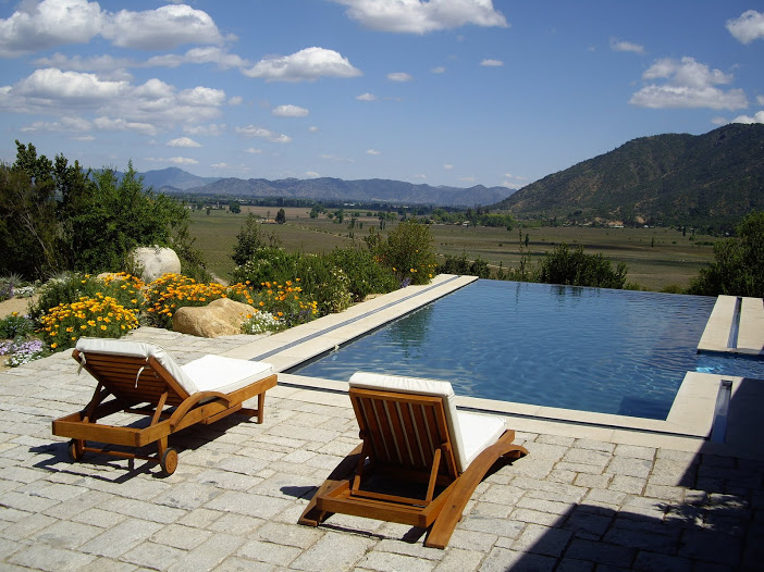 Two deck chairs at the edge of a deep blue infinity pool looking out across vineyards and mountains