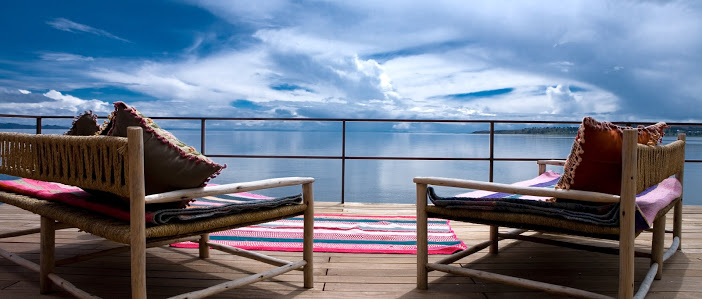 Two wooden chairs on a balcony looking out to a wide, serene lake